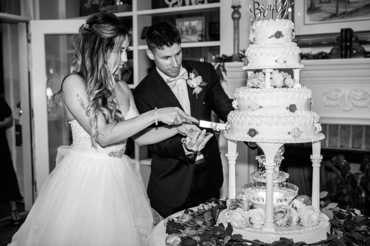husband and wife cutting cake at their wedding in savannah