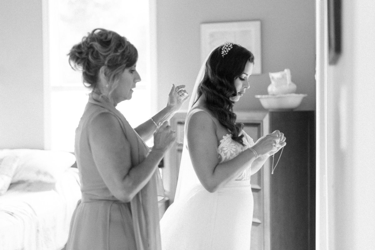 Mom helping bride put her necklace on before her wedding at The Chanterelle in Thunder Bay