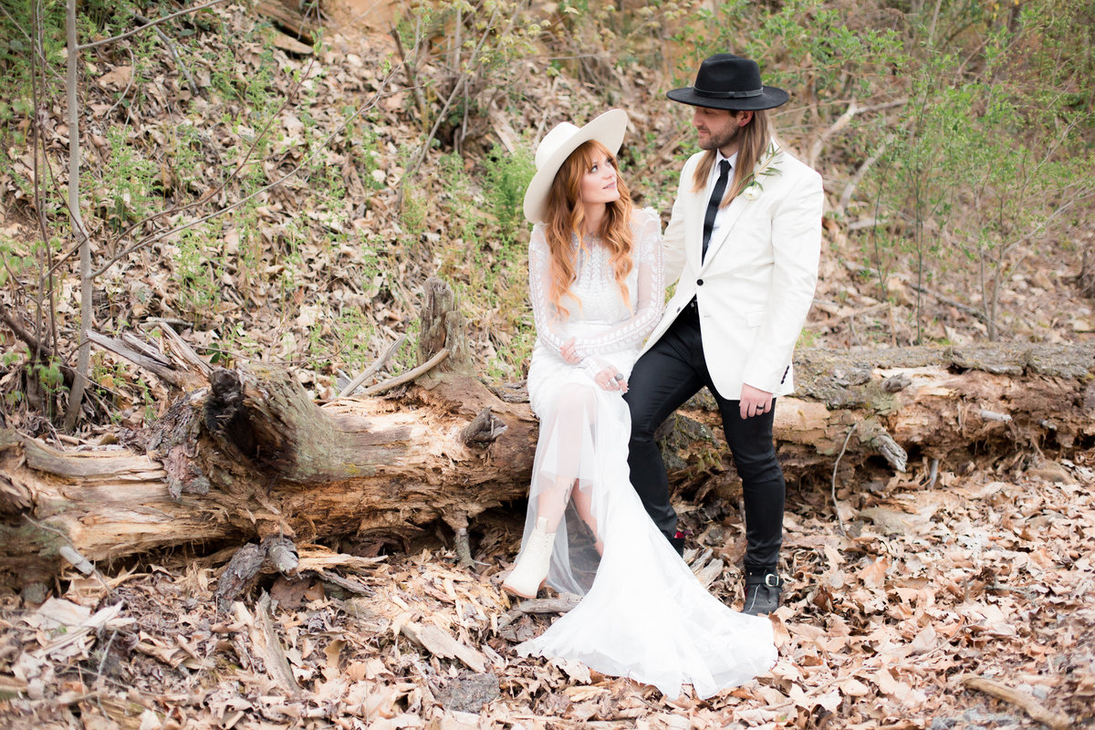 trendy couple in white with black and white hats photographed by Atlanta wedding photographer