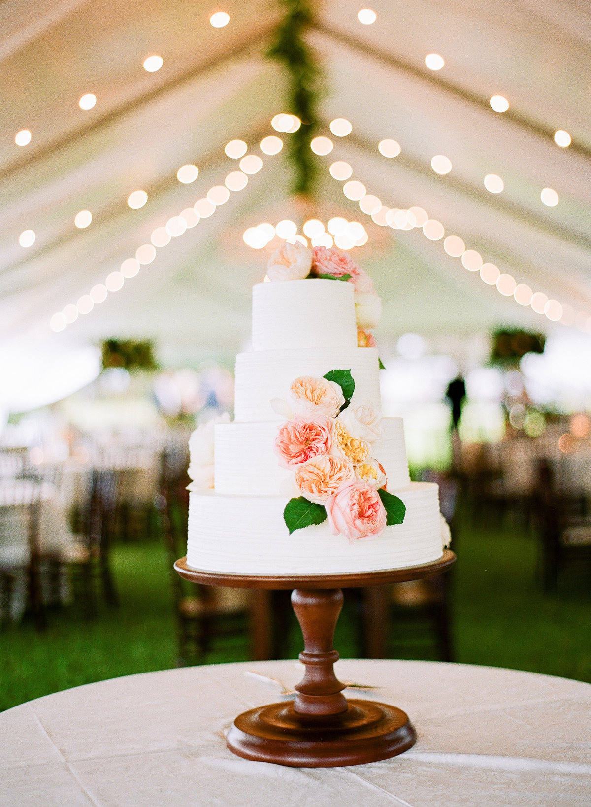 Classic Ashley Bakery Wedding Cake with White Buttercream and Fresh Blush and Peach Flowers on Wooden Mahogany  Pedestal Stand