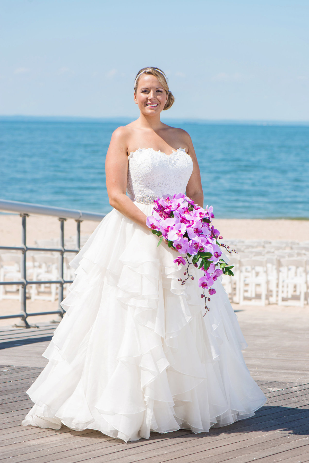 photo of bride holding bouquet on the boardwalk with beach view from wedding at Pavilion at Sunken Meadow
