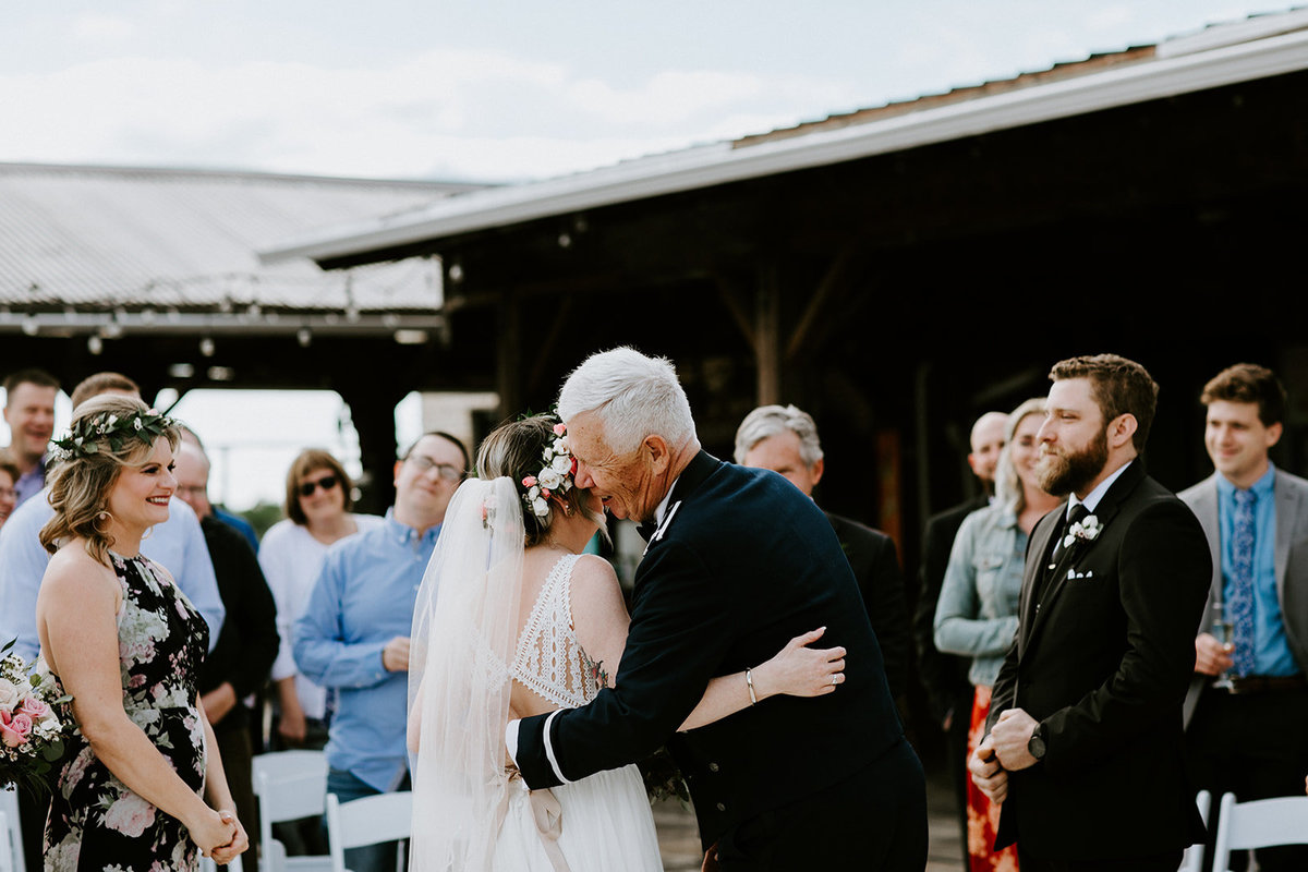 A father of the bride hugs his daughter at the end of the aisle.