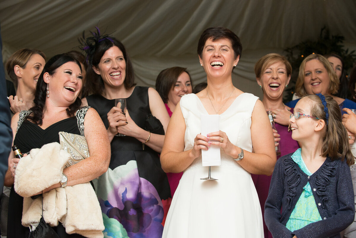 Bride and her friends listening to speeches and laughing