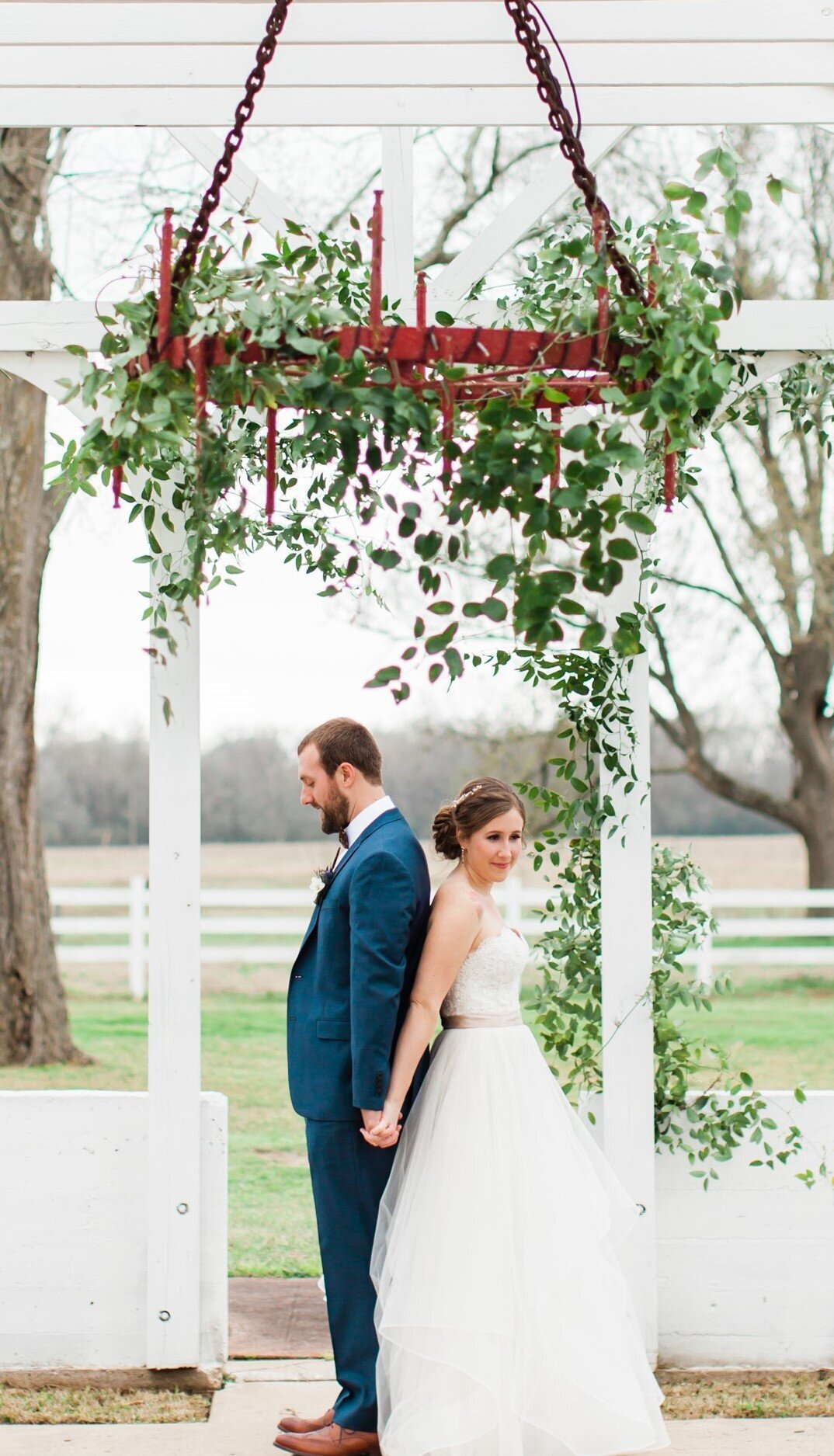 A bride and groom standing under a gorgeous red chandelier on wedding day. They are back to back getting ready for their first look