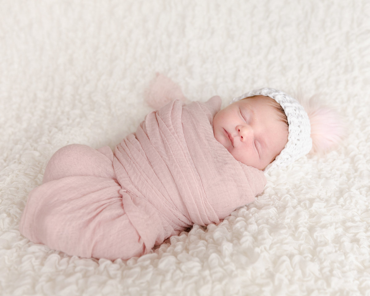 newborn baby swaddled in pink blanket on a white blanket
