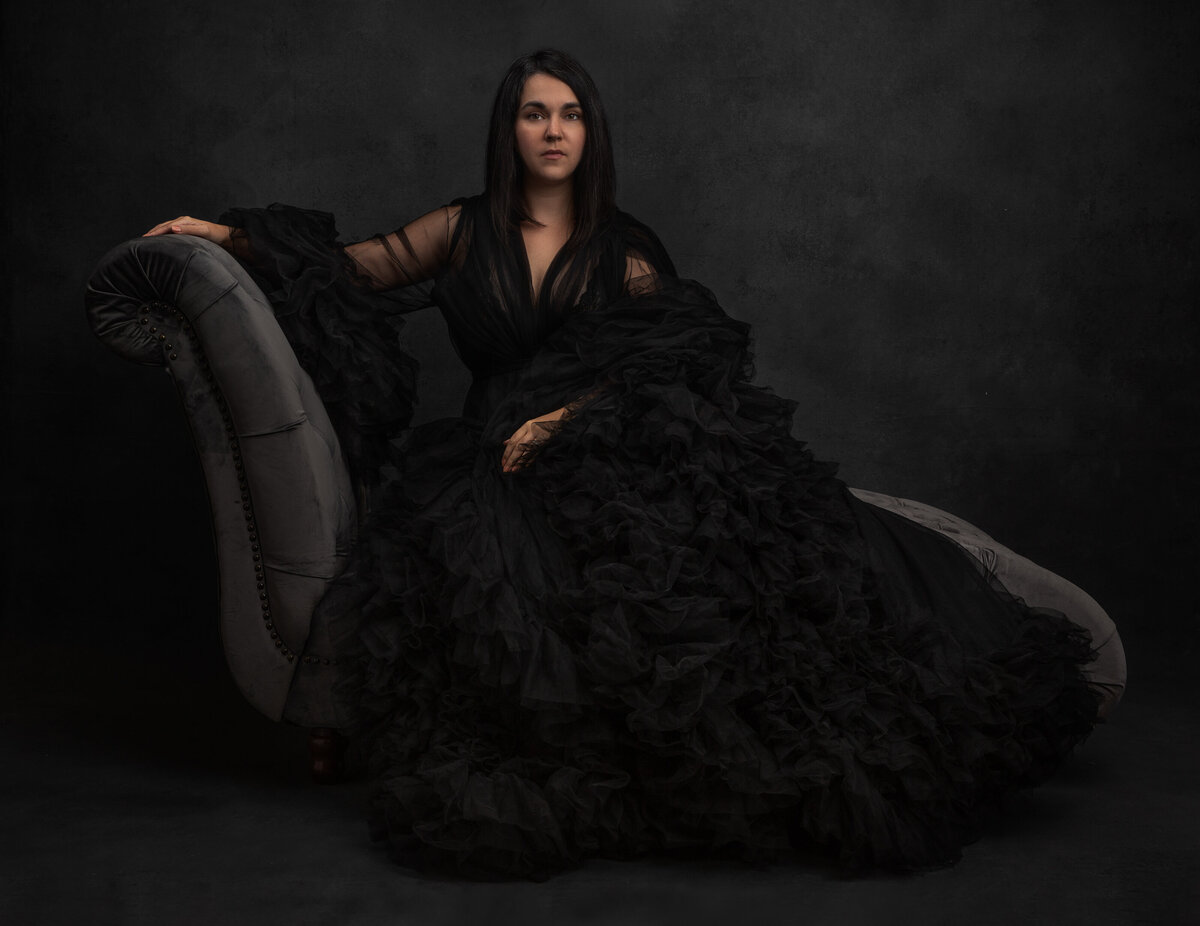 A woman with dark hair wearing a black ruffled gown poses for a beauty portrait photograph at Janel Lee Photography studios in Cincinnati Ohio