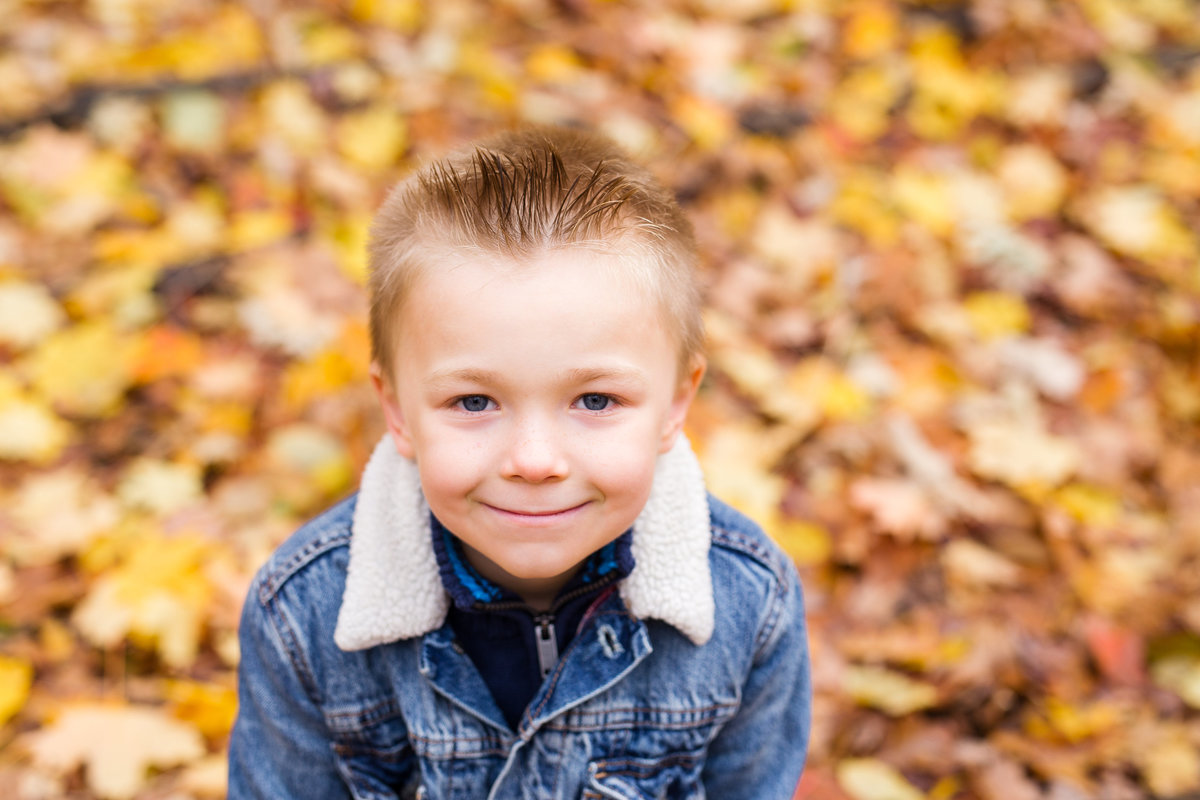 5 year old boy looking at camera and smiling in forest {Brampton Family Photographer}