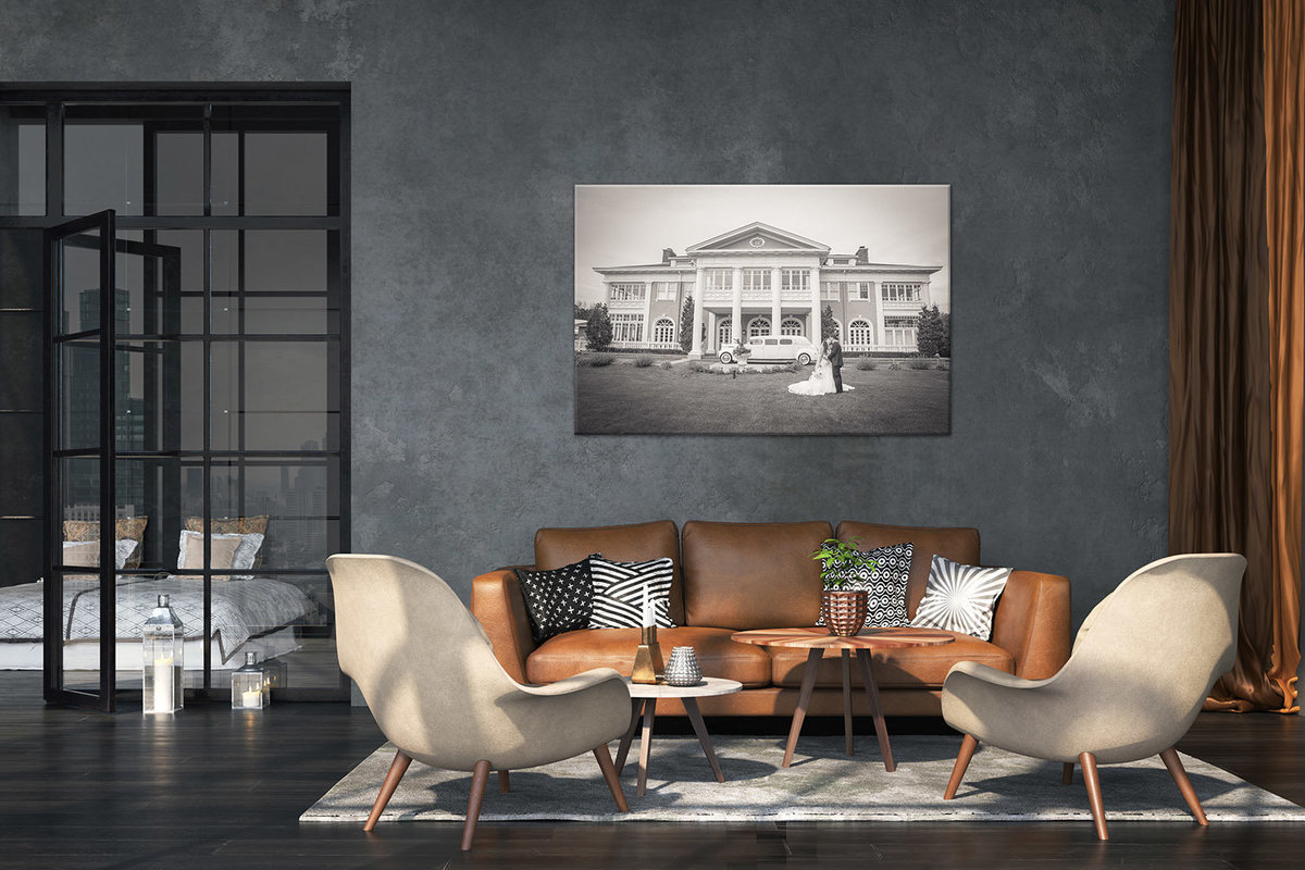 Large fine-art print in a living room with brown leather sofa and glass door.