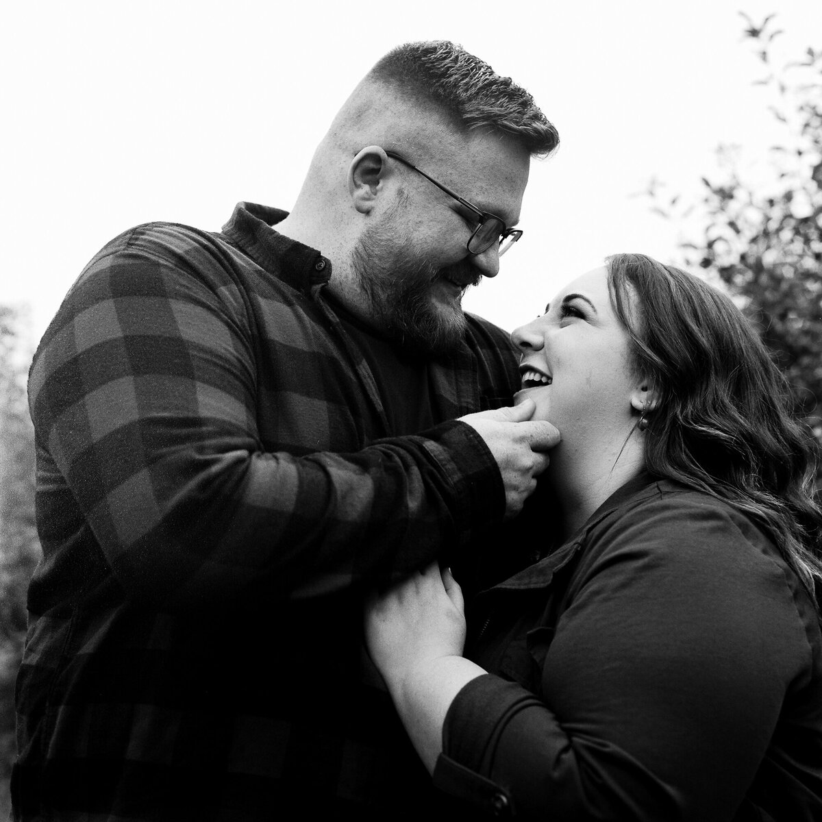Couple snuggles at Lynd's fruit farm during engagement session