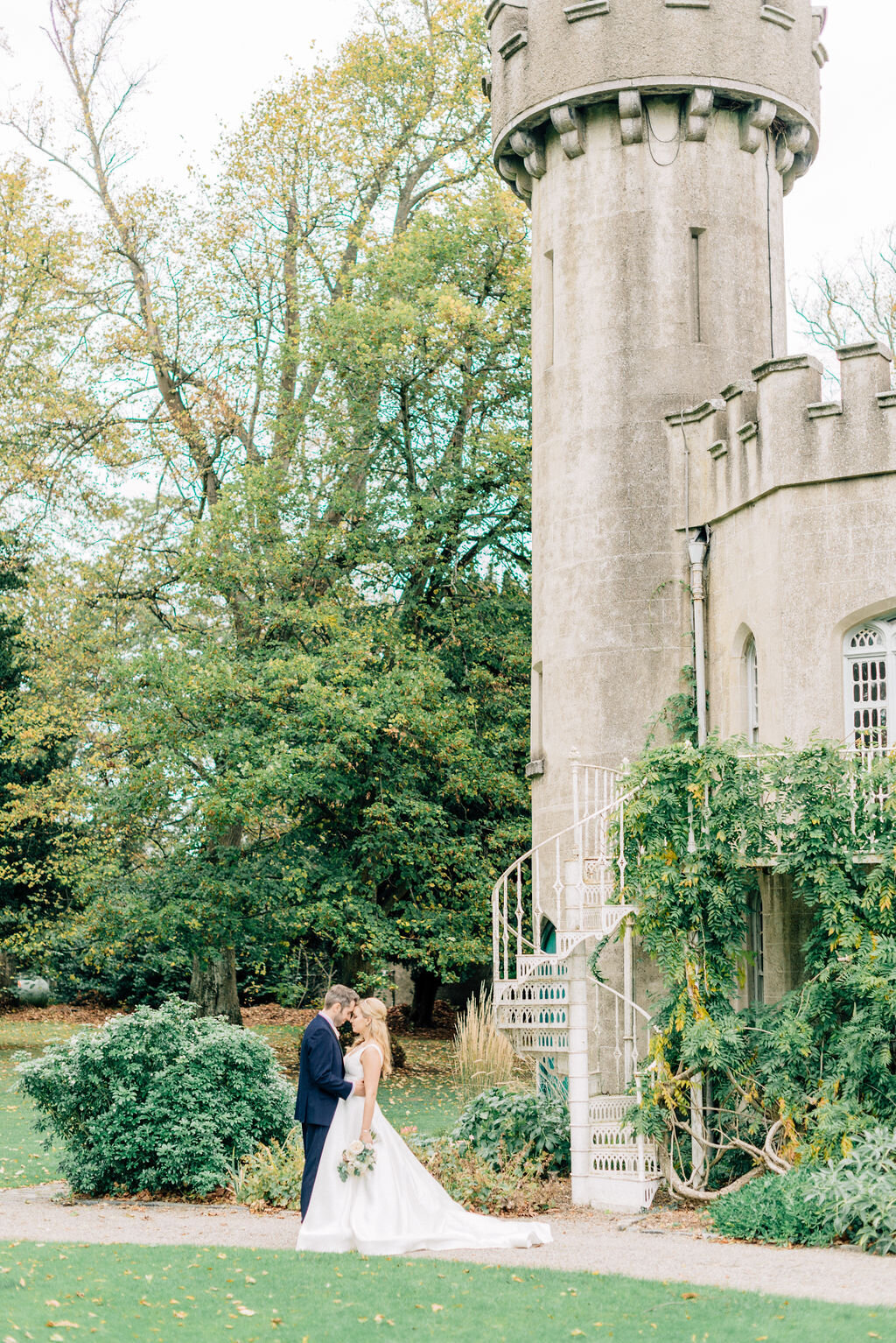 Ireland & US Wedding Planner, wide angle of couple standing on the lawn next to castle