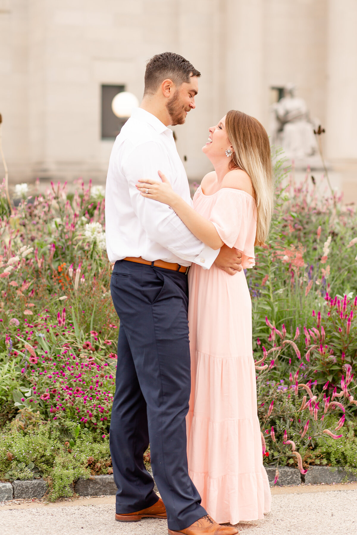 Summer Sunset Engagement Session with pink off the shoulder dress couple laughing by wildflowers at St. Louis Art Museum in Forest Park in St. Louis by Amy Britton Photography Photographer in St. Louis