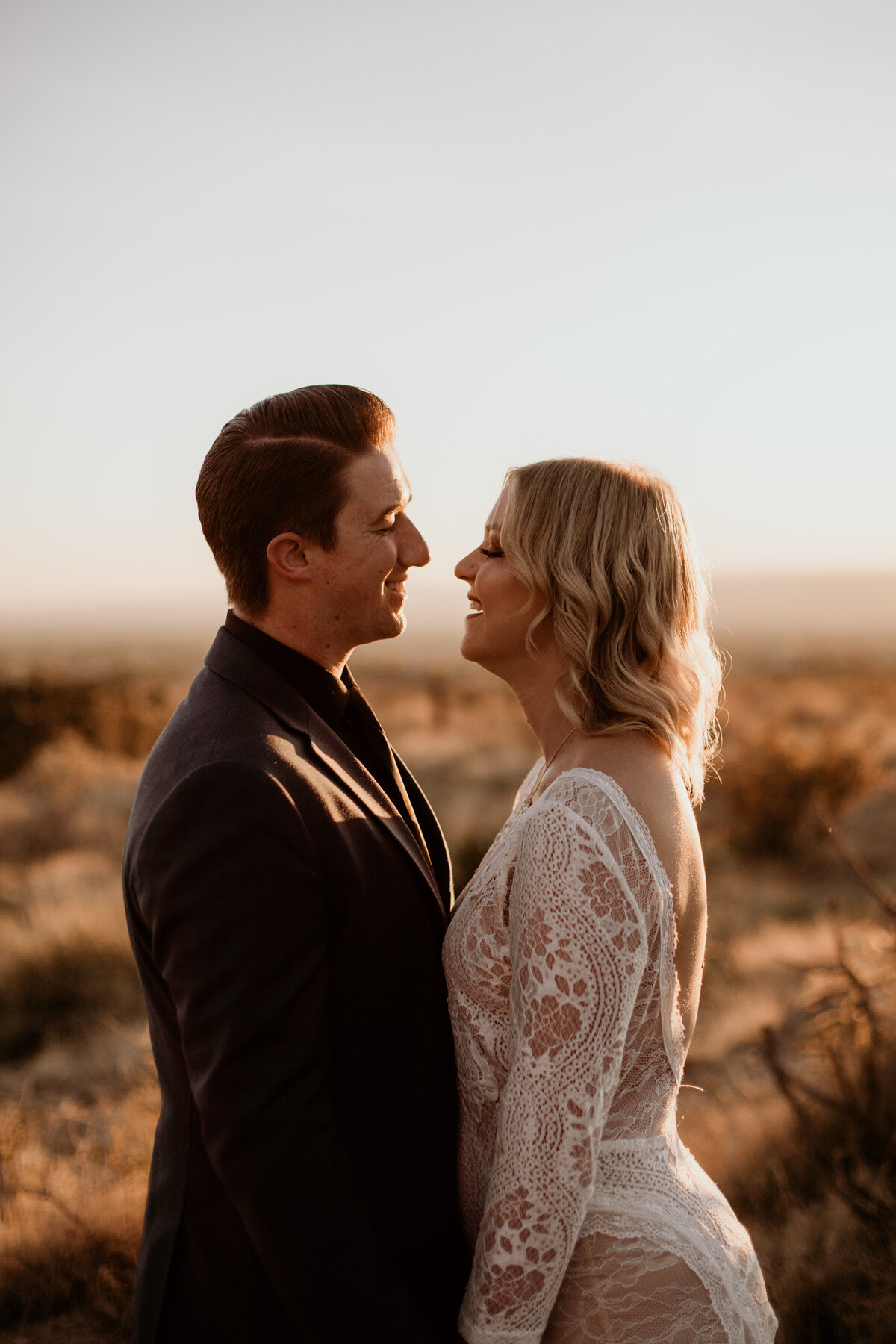 husband and wife looking at each other at sunset