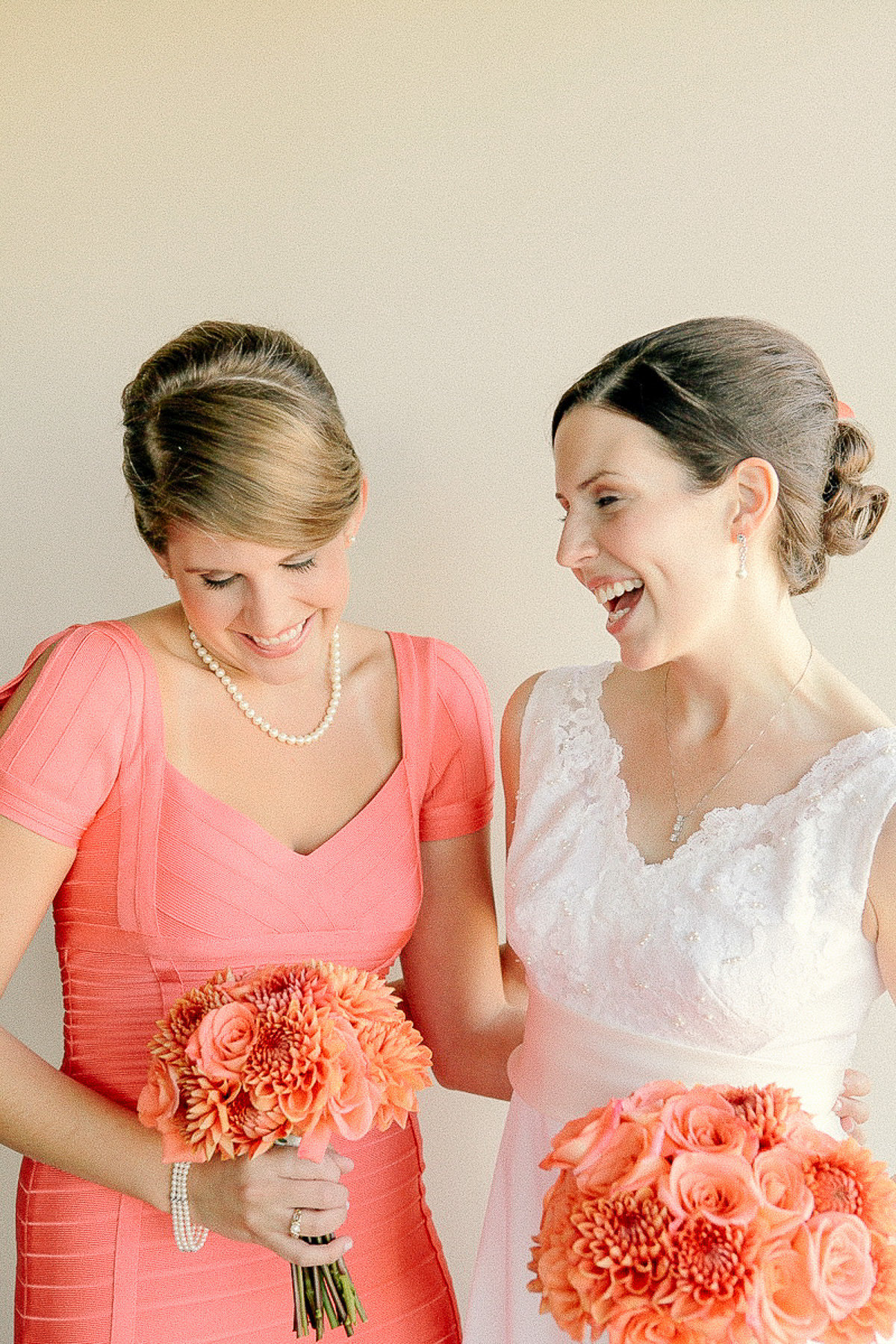Bride with maid of honor holding peach and orange bouquets