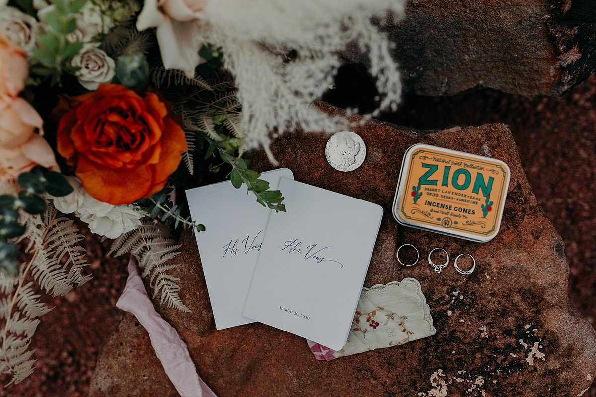 Groom and Bride's wedding bouquet, vow books, and rings are styled on a large rock