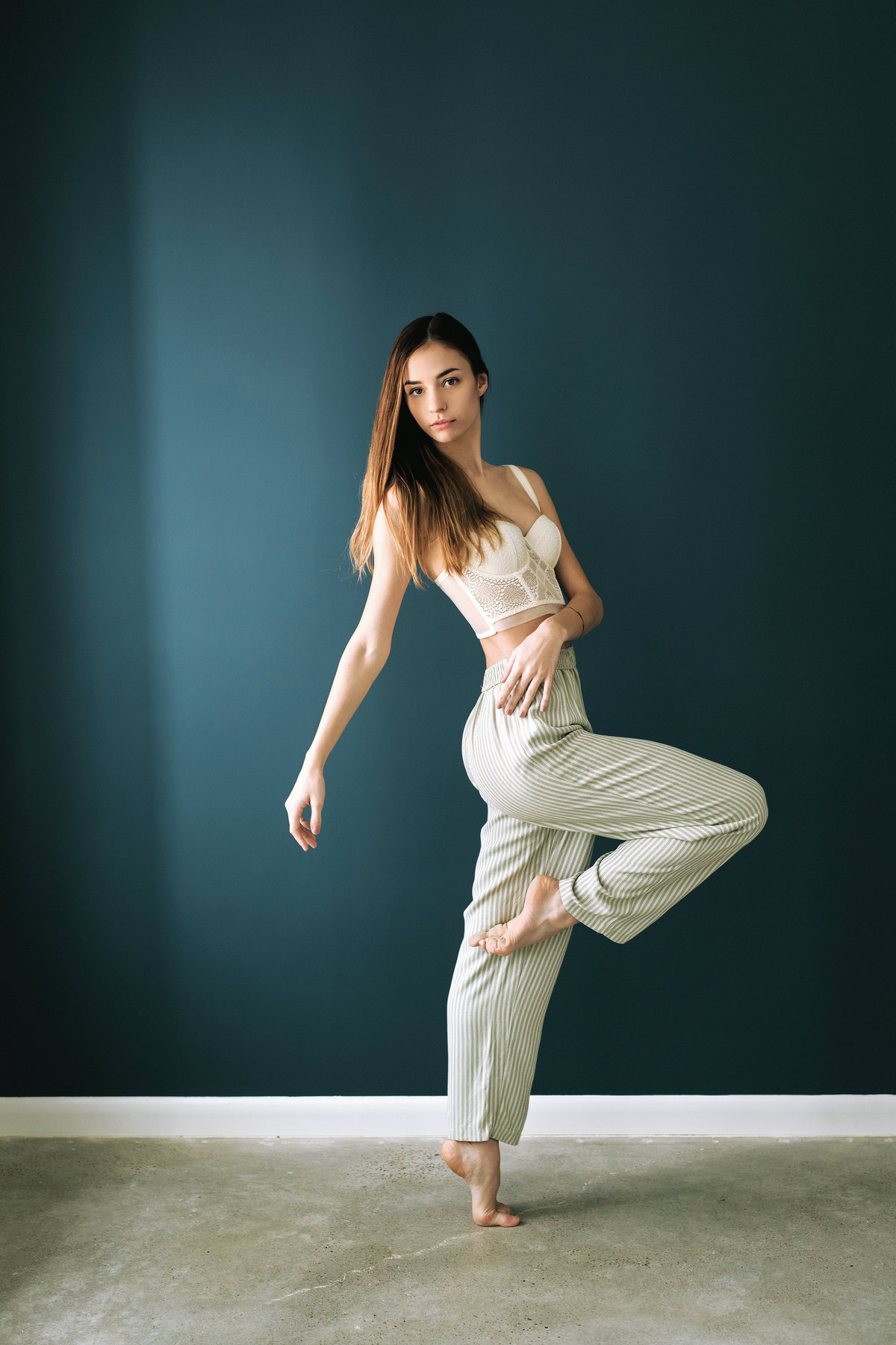 Brightly lit portrait of woman in dance pose looking camera center.