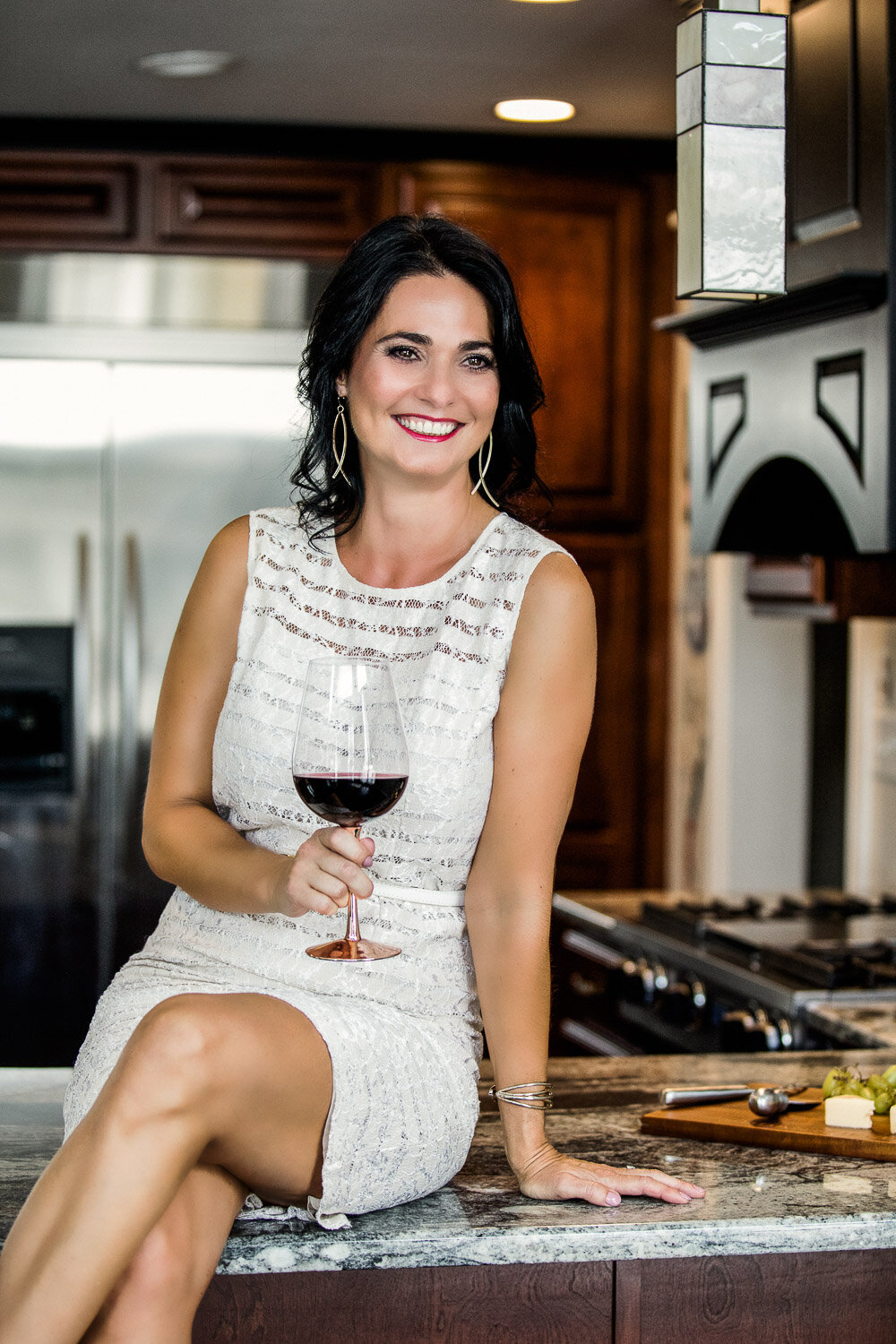 Woman sitting on kitchen counter with glass of wine