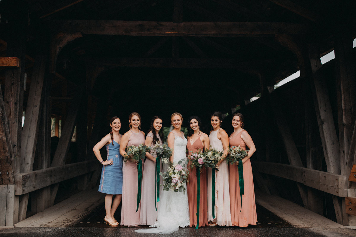 Bride and bridesmaids under covered bridge