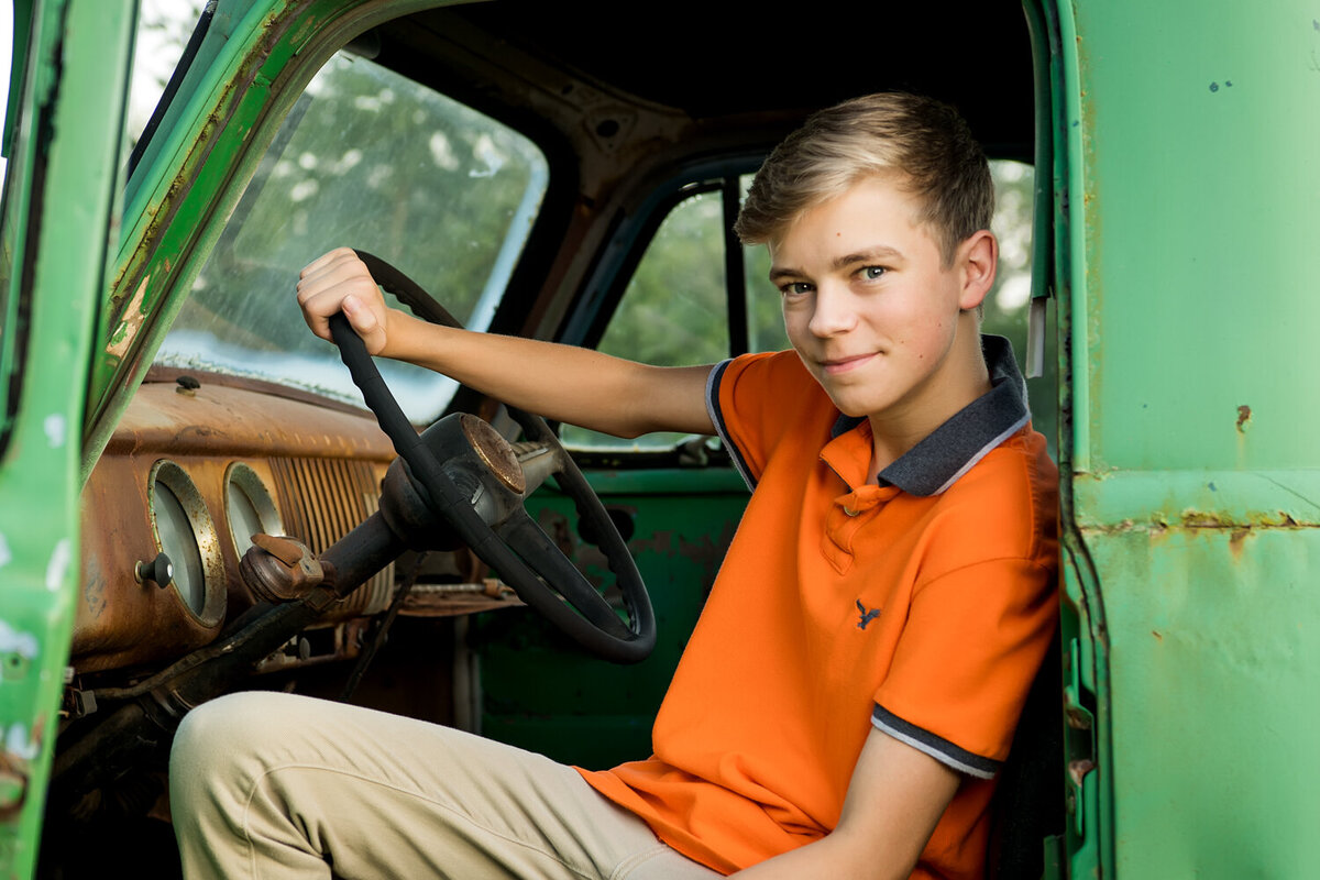 Senior boy vintage truck vintage inside portrait park orange shirt rusty truck