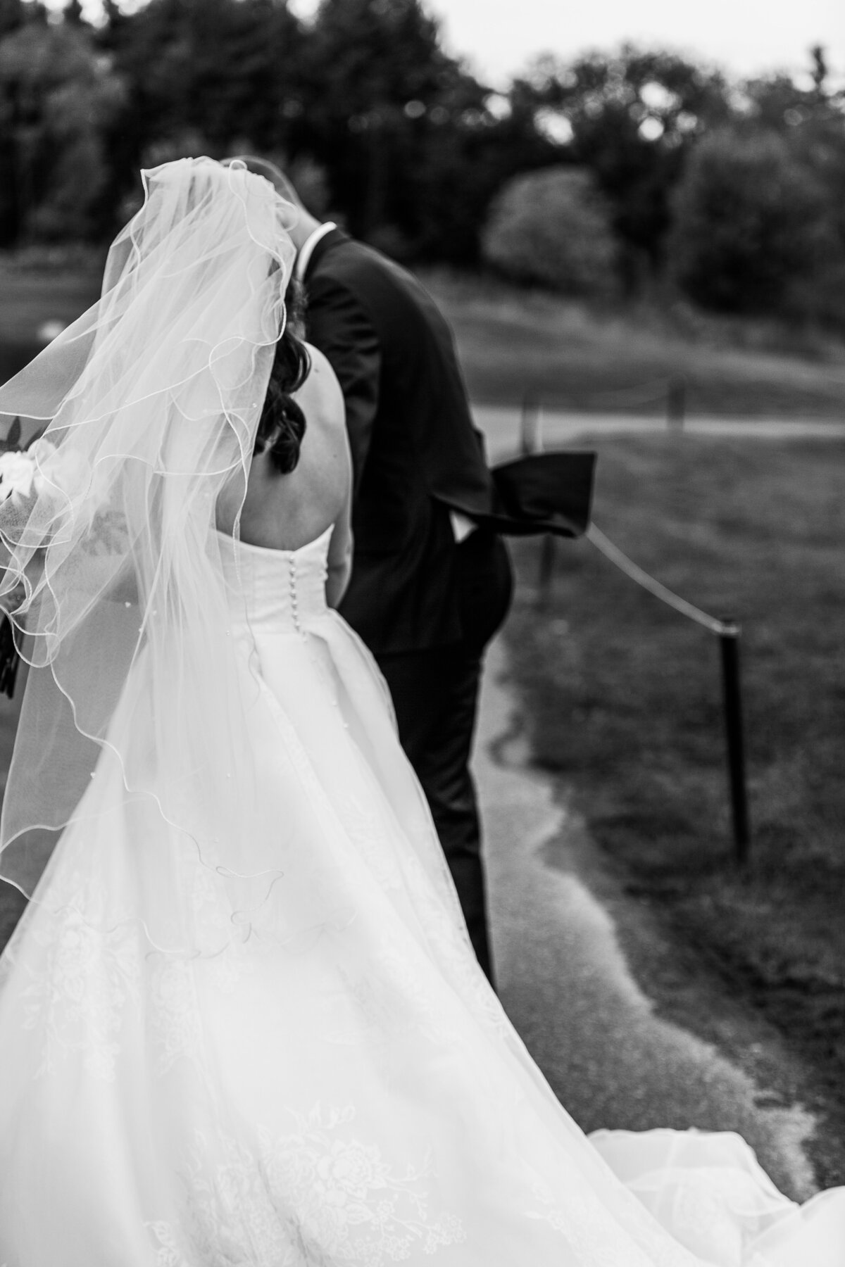 black and white photo of bride and groom walking away outside
