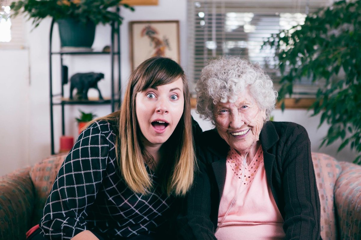 A woman sits with her grandmother laughing