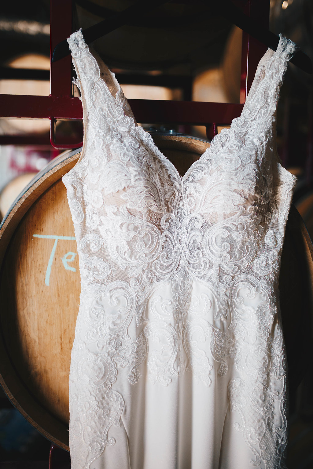 lace wedding dress hanging in the barrel room of a winery