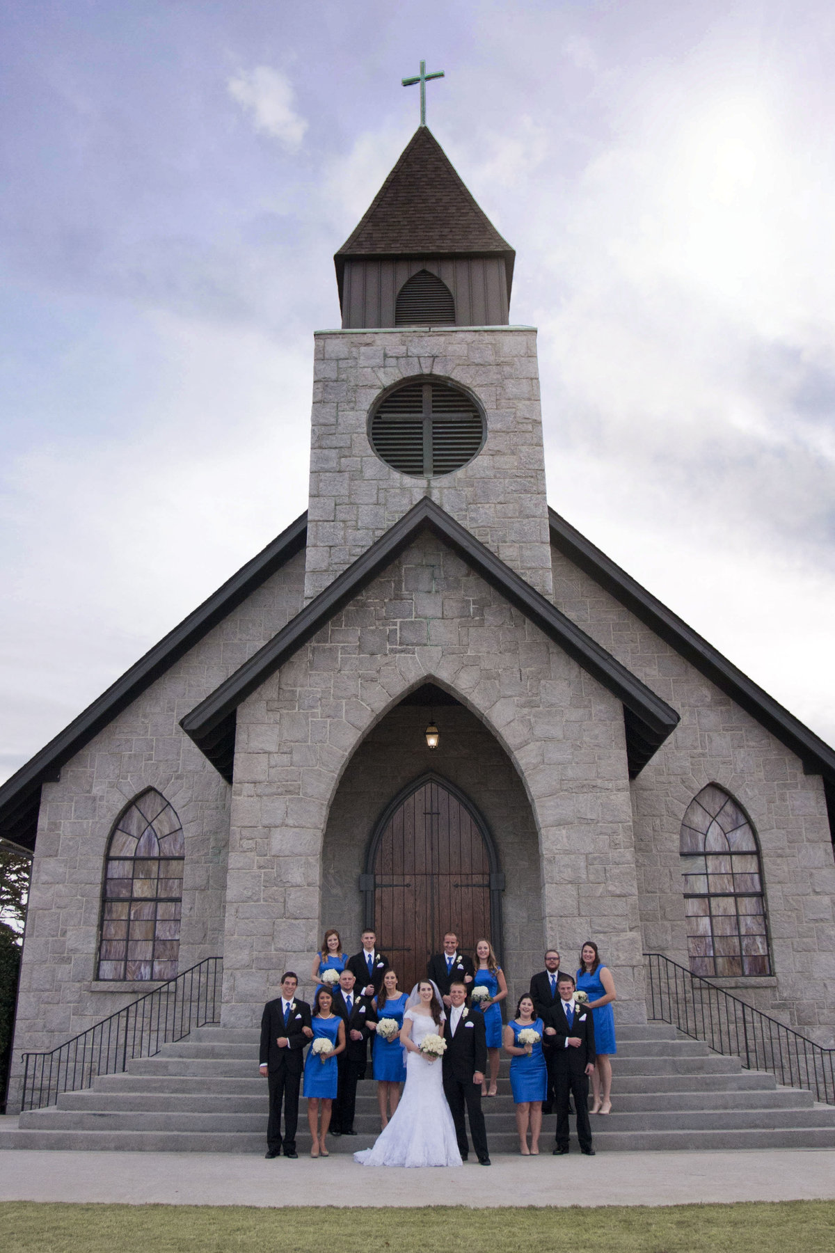 Bridal Party in front of stone church in royal blue