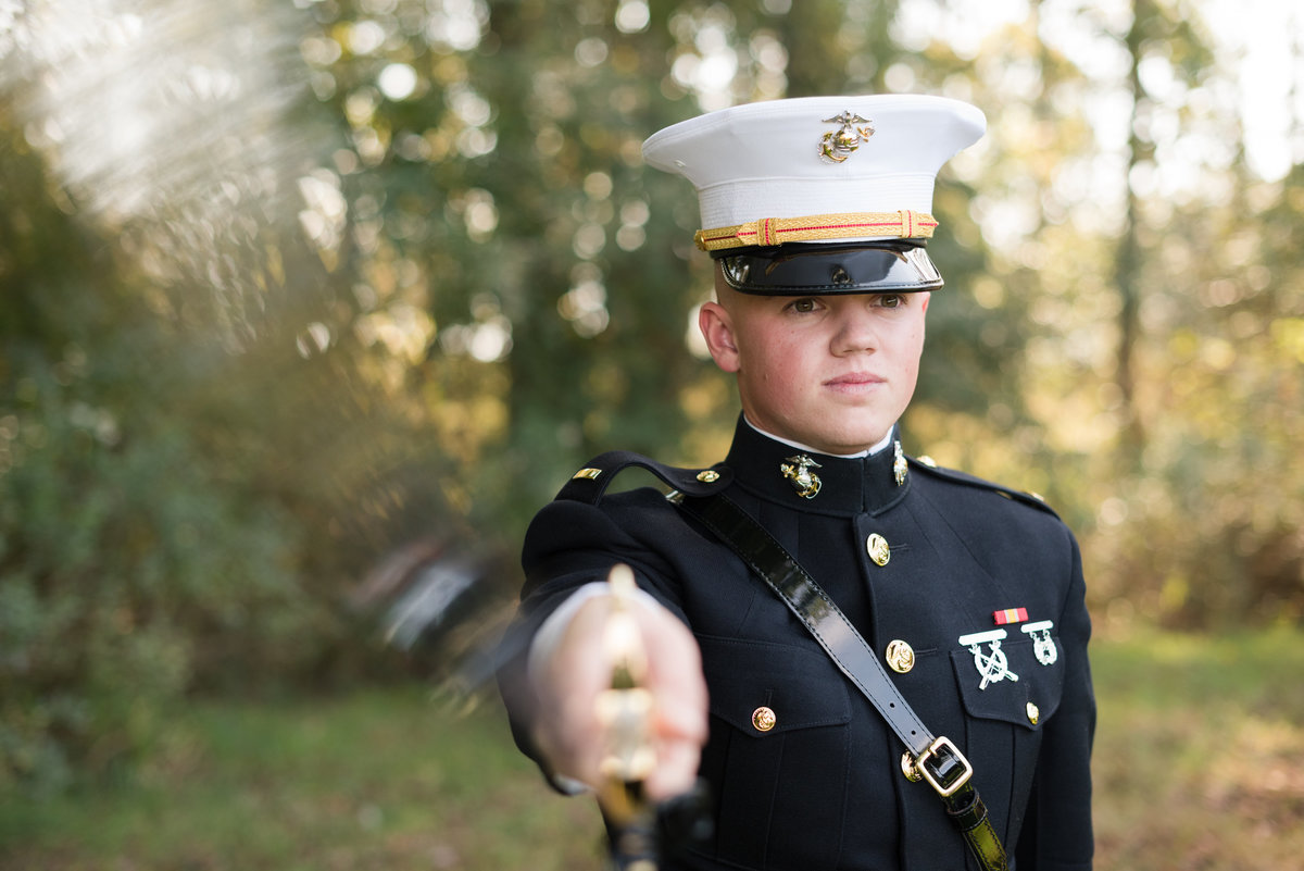marine corps officer groom shows sword during two rivers country club wedding by williamsburg virginia photographer