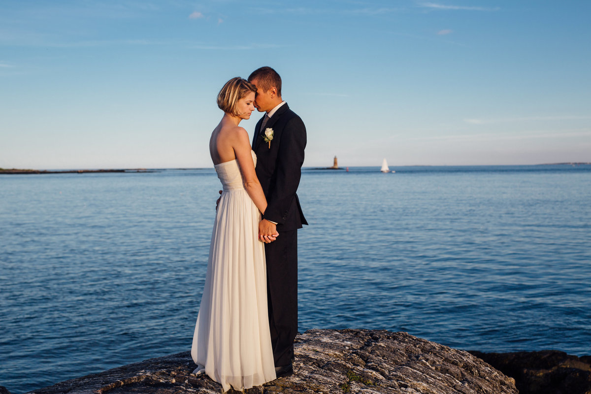 The newly eloped couple hold each other close on the rocks in New Castle NH