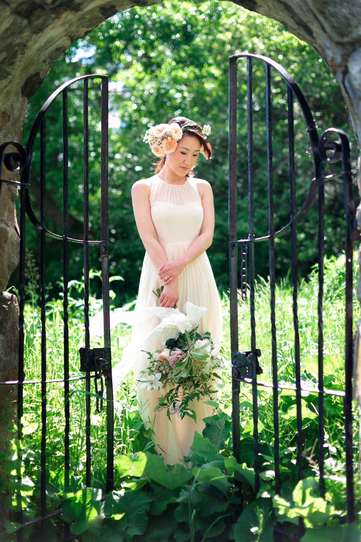 The bride is framed by a stone wall and gate while among the plants on her wedding day at Inn at Castle Hill at Barn at Crane Estate wedding