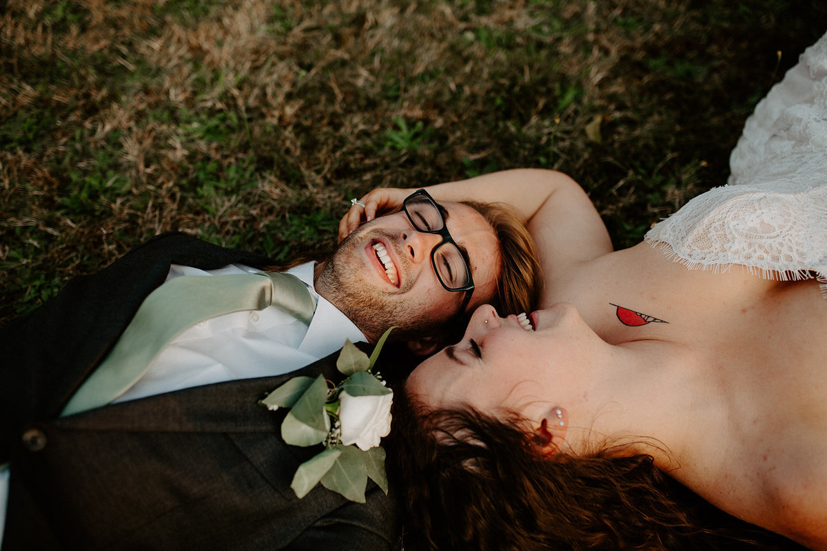 Bride and Groom laying on the grass for bridal portraits on their wedding day