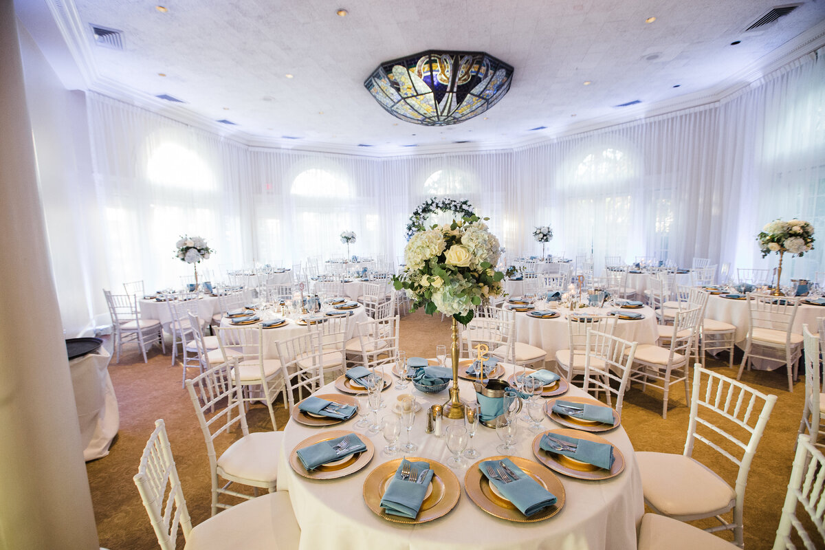 Soft sunlight peeks through the drapes as the guest tables are captured moments before the reception is to begin.