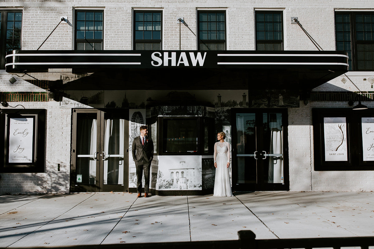 A bride and groom stand apart in front of a building.