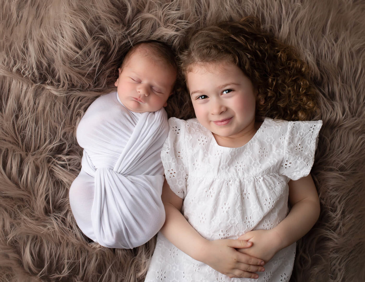 Newborn boy and big sister posed together on a flokati in Rochester, NY.