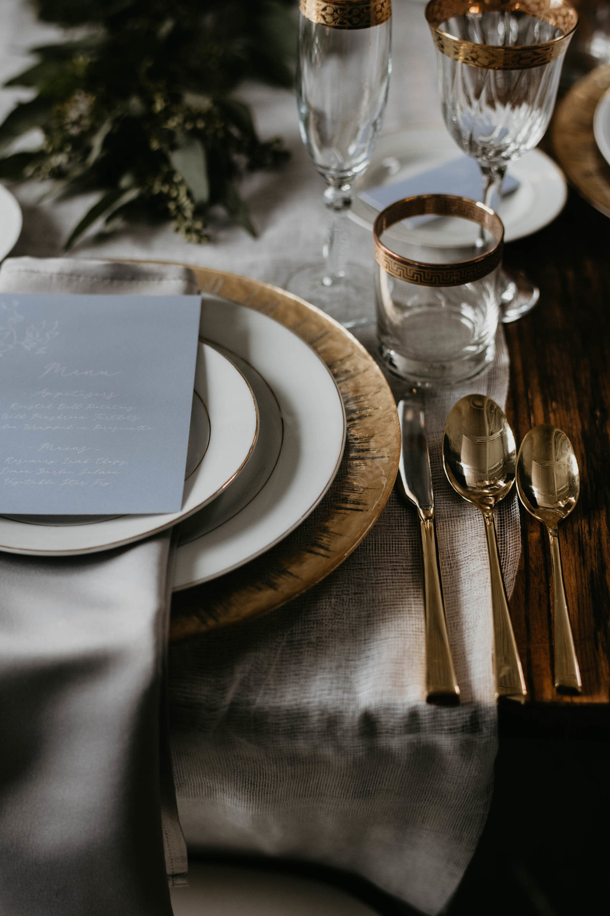 head of the table set with gold cutlery, charger plate and cheese cloth table runner