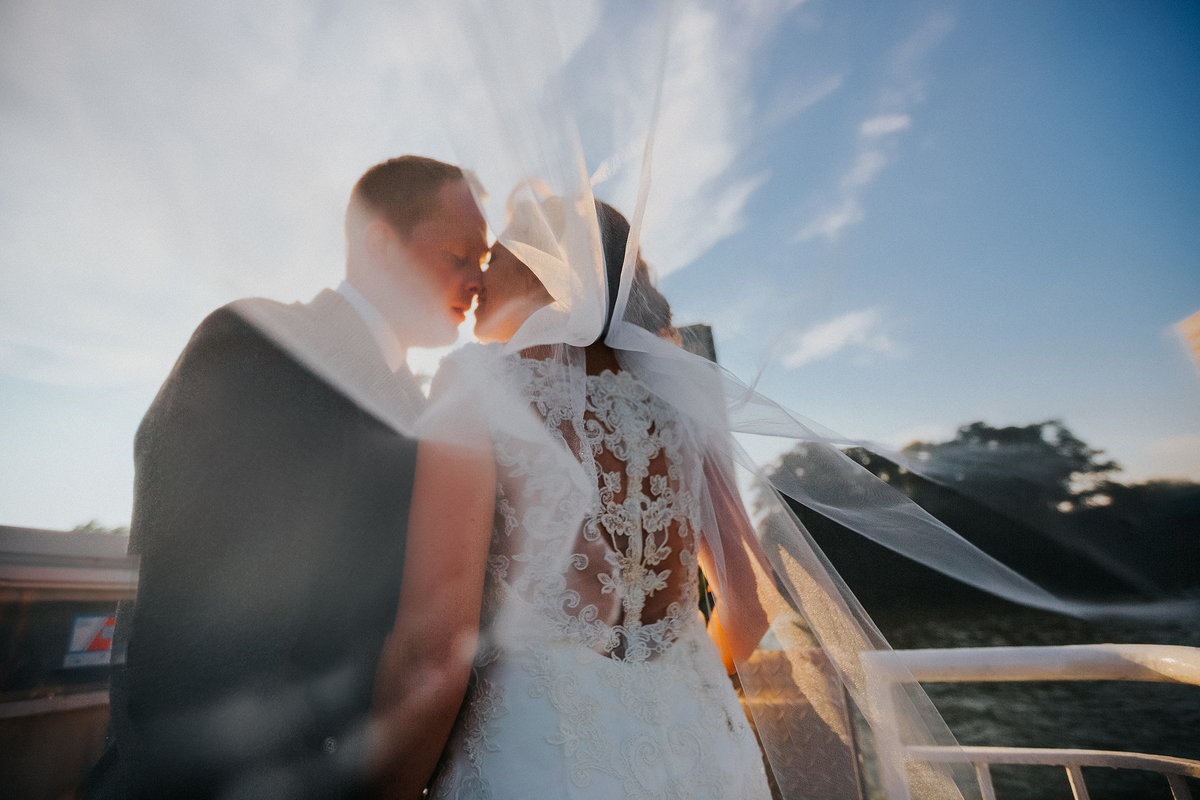 bride and groom kissing under veil on rock river in rockford illinois