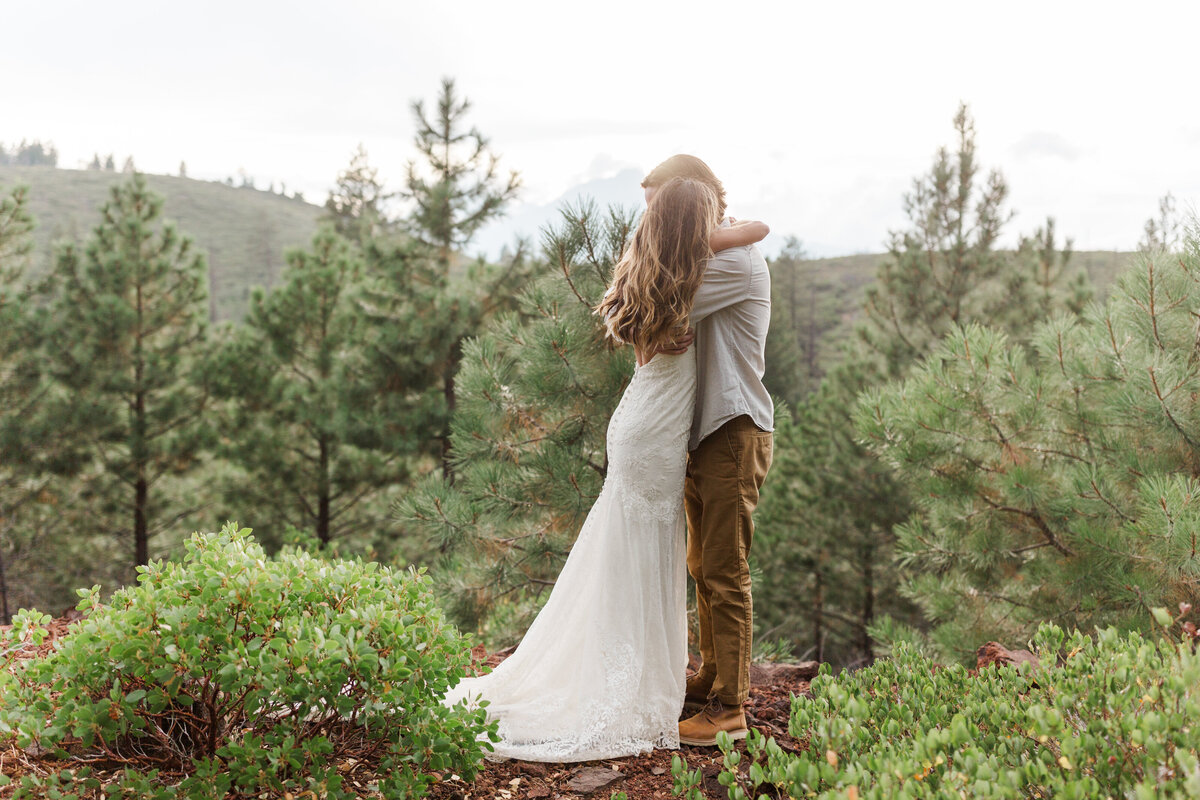 Bride and groom hug duringsunset  mountaintop elopement surrounded by pine trees in Bend, Oregon. The bride is wearing a low back lace dress with long train, and the groom is wearing boots and hiking pants.