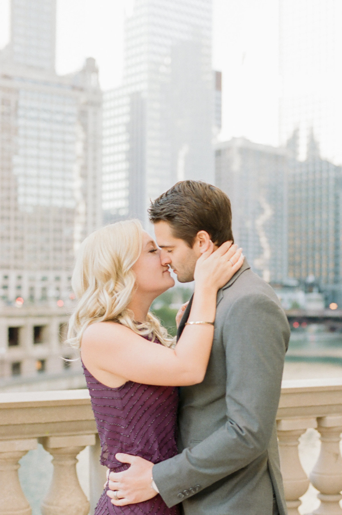 engaged couple kissing in front of chicago skyline