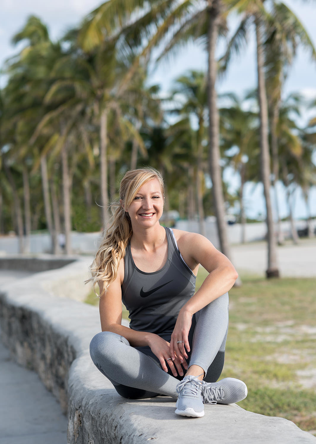 Woman in athletic clothing sitting by the beach