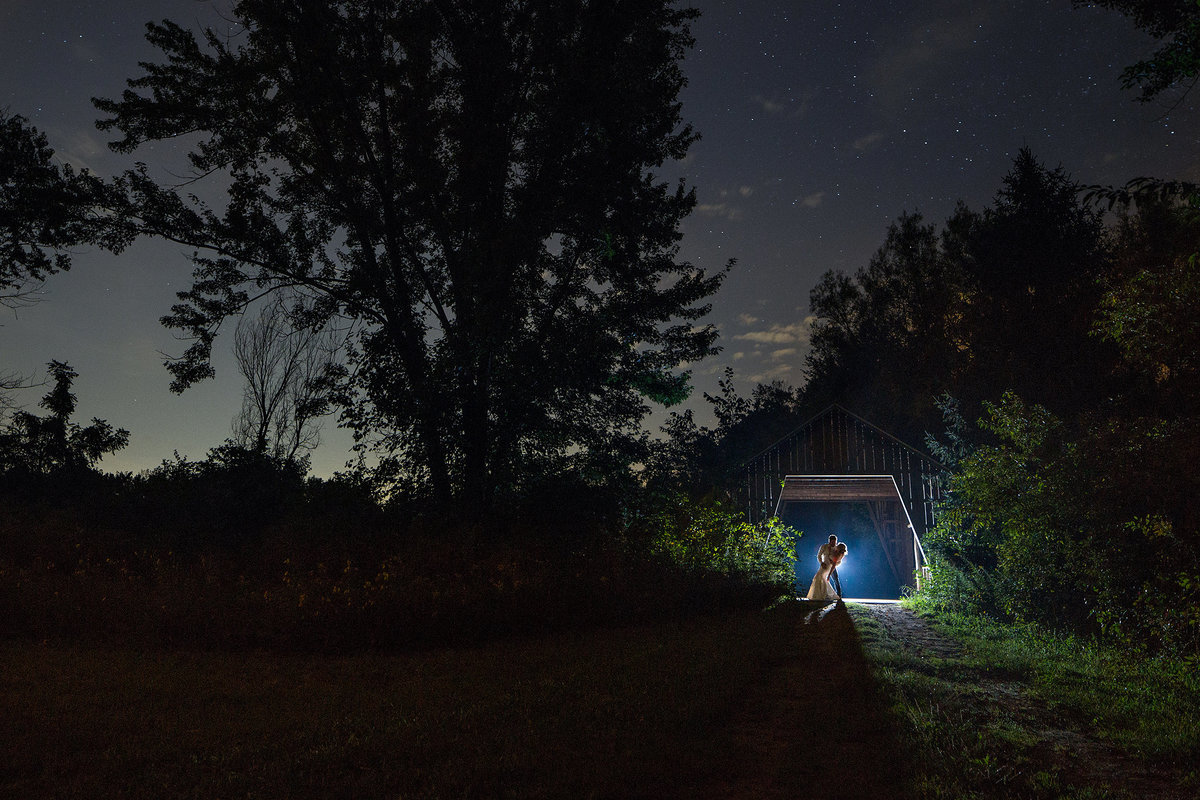 nighttime photograph of a couple under a covered bridge at williams tree farm in rockton illinois