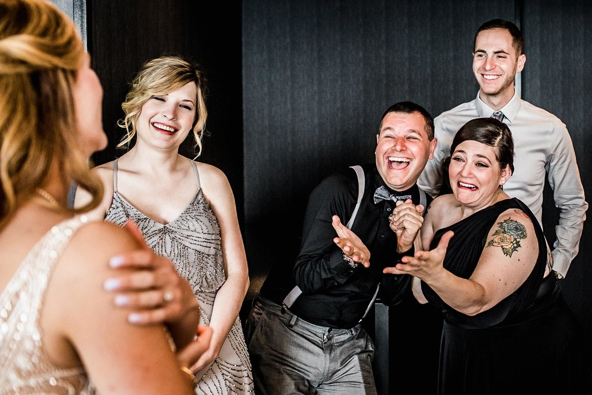 A wedding party reacts to seeing the bride for the first time at a W Hotel Chicago wedding.