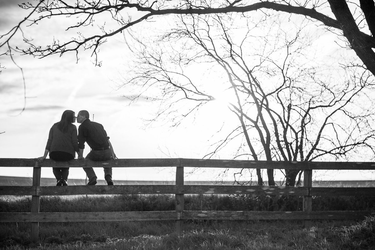 couple sitting on a fence and kissing during their engagement photographs