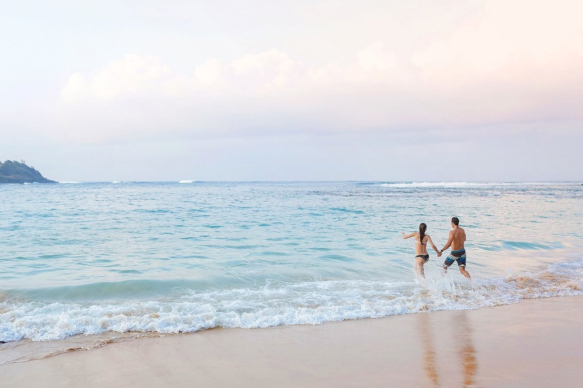 Engaged Maui couple run into the ocean hand-in-hand