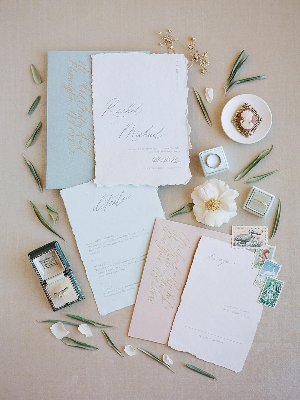 Wedding invites written in calligraphy surrounded by flowers, vintage rings and stamps