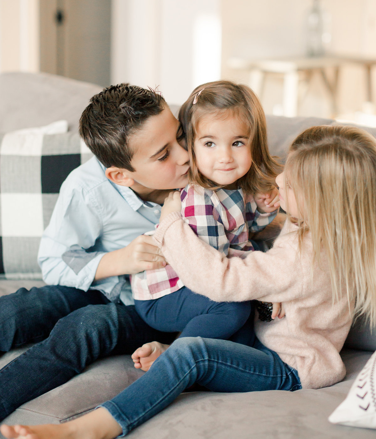 very sweet siblings of young sister cuddle on couch for lifestyle family photography
