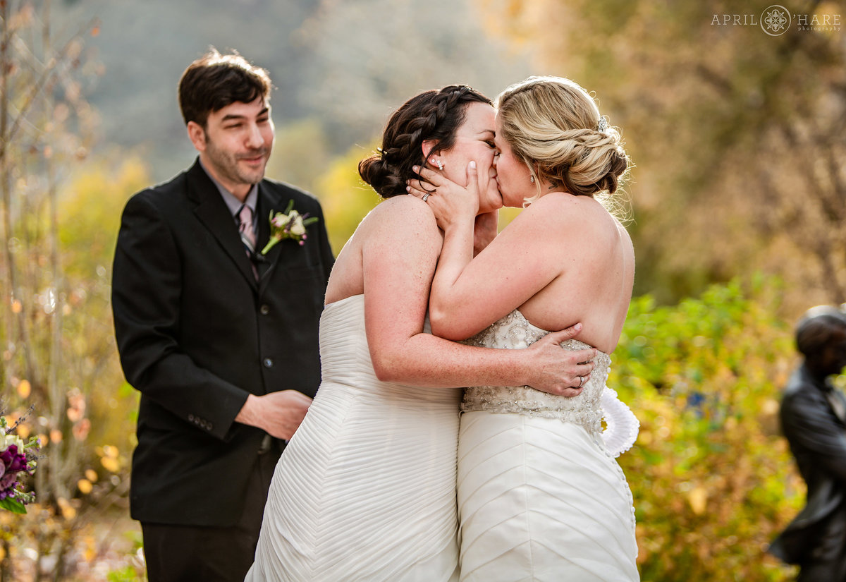 Two brides kiss at their outdoor Golden Hotel Wedding at a same sex wedding ceremony in Colorado during autumn