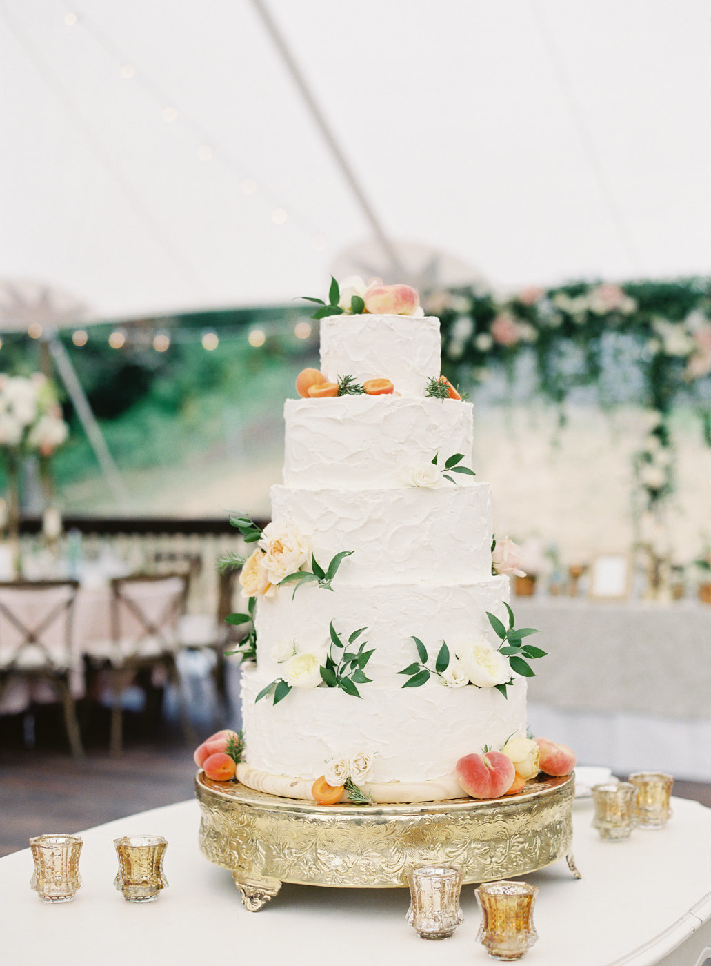 White layer cake decorated with roses, greens and peaches along with gold accents.