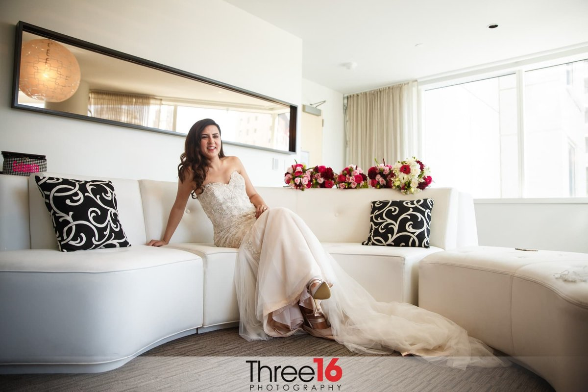 Bride sitting on a bridal suite  couch posed in her wedding dress