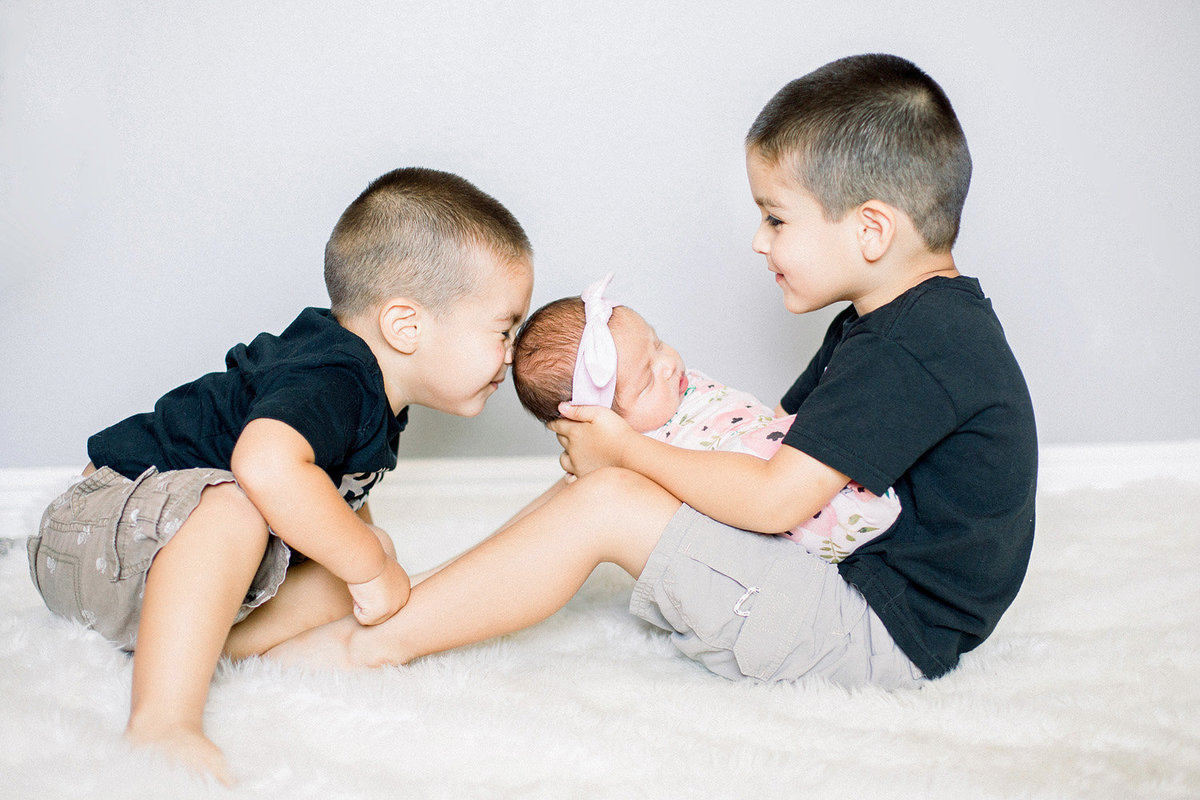big brothers with their baby sister