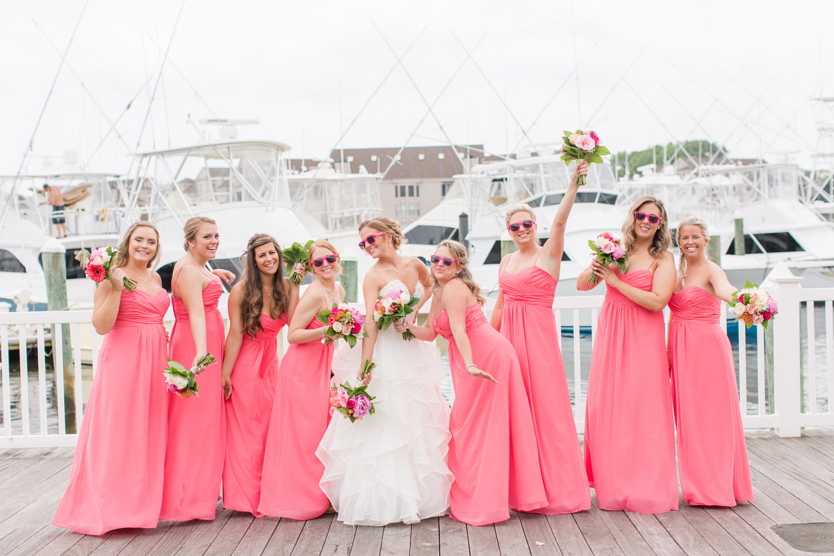 Bride and bridesmaids posing in coral dresses and sunglasses at The Water Table