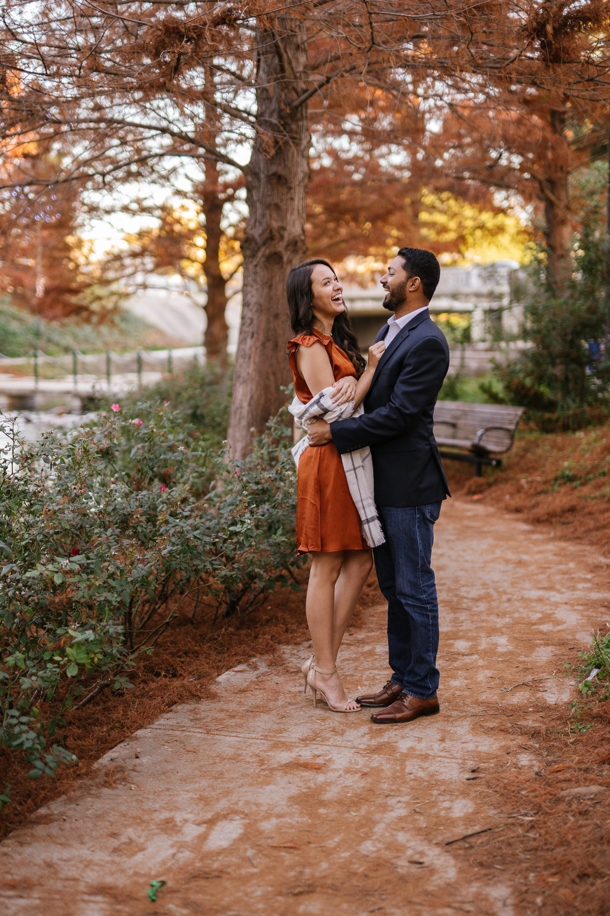 Beautiful fall engagement session for couple with leaves on the ground and standing next to a river.